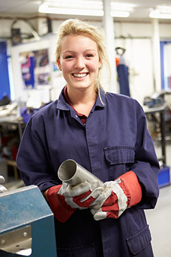 Female apprentice engineer working on a factory floor